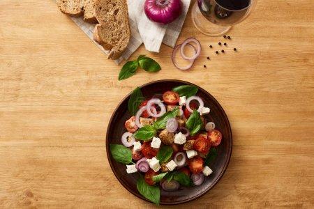 Photo pour Vue du dessus de la délicieuse salade de légumes italienne panzanella servi sur une assiette sur une table en bois près d'ingrédients frais sur une serviette et du vin rouge - image libre de droit