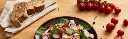 Photo for Delicious Italian vegetable salad panzanella served on plate on wooden table near tomatoes and bread, panoramic shot - Royalty Free Image