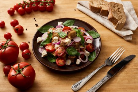 Photo for Delicious Italian vegetable salad panzanella served on plate on wooden table near fresh tomatoes, bread, fork and knife - Royalty Free Image