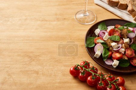 Photo for Delicious Italian vegetable salad panzanella served on plate on wooden table near fresh tomatoes, bread - Royalty Free Image
