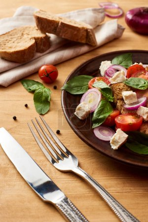 Photo for Delicious Italian vegetable salad panzanella served on plate on wooden table near cutlery - Royalty Free Image