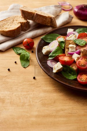 Photo for Delicious Italian vegetable salad panzanella served on plate on wooden table near fresh ingredients and bread - Royalty Free Image