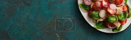 Photo pour Vue du dessus de délicieuse salade de légumes italienne panzanella servi sur assiette sur surface verte texturée, vue panoramique - image libre de droit