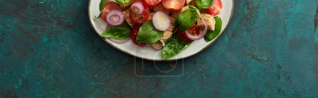 Photo for Top view of delicious Italian vegetable salad panzanella served on plate on textured green surface, panoramic shot - Royalty Free Image