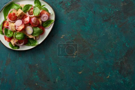 Photo for Top view of delicious Italian vegetable salad panzanella served on plate on textured green surface - Royalty Free Image