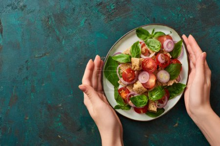 cropped view of woman holding plate with delicious Italian vegetable salad panzanella on textured green surface