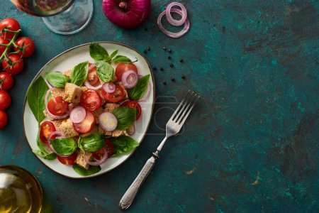 Photo for Top view of delicious Italian vegetable salad panzanella served on plate on textured green surface with ingredients and fork - Royalty Free Image