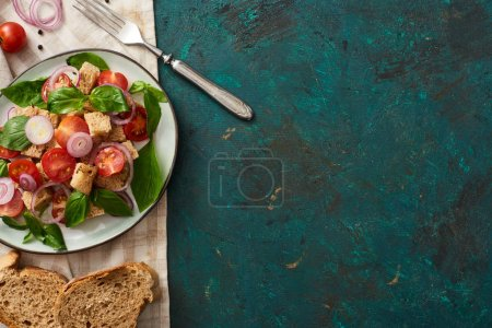 top view of delicious Italian vegetable salad panzanella served on plate on textured green surface with bread, ingredients, napkin and fork