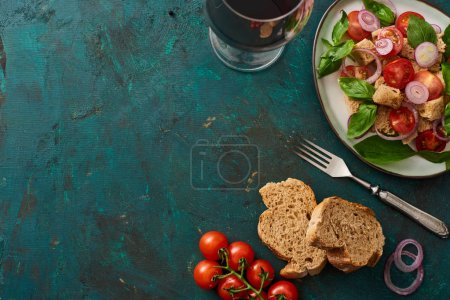 top view of delicious Italian vegetable salad panzanella served on plate on textured green surface with tomatoes, bread, red wine and fork