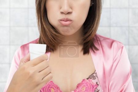 Asian Woman rinsing and gargling while using mouthwash.