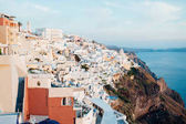 Traditional view of the island of Santorini at sunset with white, blue and orange buildings, overlooking the blue sea, sky and islands, horizontal