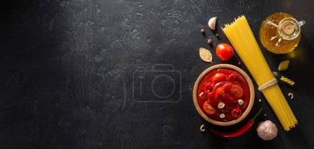 Photo for Tomato sauce in bowl on black background texture - Royalty Free Image