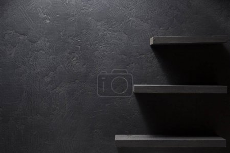 wooden shelf at black wall