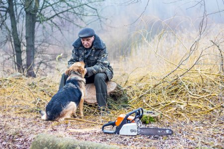 a man, a forester, sits on a stump, near him a dog, they communi