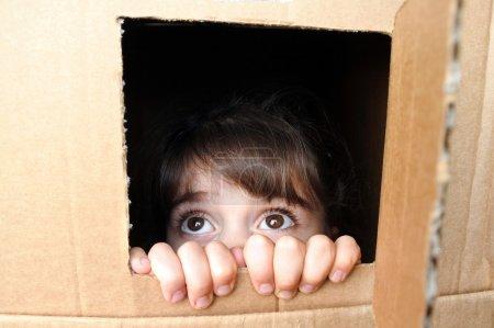 Photo pour Visage de petite fille effrayée regardant hors d'une boîte en carton se cachant de quelqu'un. Concept de violence envers les enfants. espace de copie - image libre de droit
