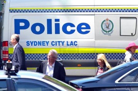 Photo pour SYDNEY - 20 OCT 2016 : Des gens passent près du véhicule de la police de Sydney Les Australiens croient que le gouvernement doit prévenir les attaques terroristes sur le sol national, mais craignent que les musulmans soient sous surveillance accrue - image libre de droit