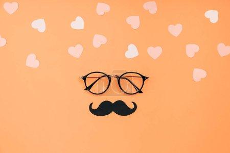 Foto de Eyeglasses, el elegante mostrador de fotos en papel negro sostiene los bigotes y muchos corazones pequeños en el fondo naranja. Copie el espacio para las inscripciones. Concepto de vacaciones del Día del Padre. - Imagen libre de derechos