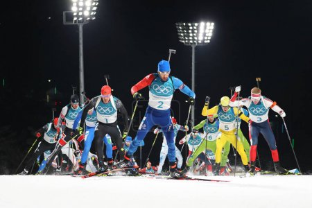 PYEONGCHANG, SOUTH KOREA  FEBRUARY 18, 2018: Olympic champion Martin Fourcade of France (number 2 in front) competes in the biathlon men`s 15km mass start at the 2018 Winter Olympics in Alpensia Biathlon Centre