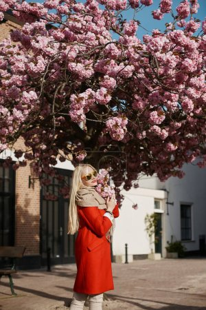 Photo for Side view of a beautiful blonde model girl wearing sunglasses and red coat posing near the pink blooming tree and looking at the camera. Happy young woman walking and enjoying sunny weather. Concept - Royalty Free Image