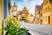 Classic view of the medieval town of Rothenburg ob der Tauber with blooming flowers on a beautiful sunny day with blue sky and clouds in springtime, Bavaria, Germany