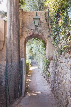 Beautiful ancient arch with lantern on cozy street...
