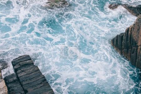 beautiful wavy sea with rocks at coastline in Riomaggiore, Italy
