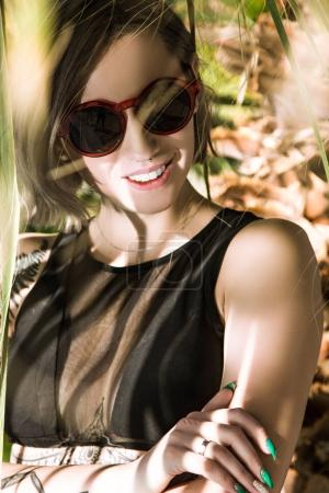 Photo for Beautiful young woman in sunglasses smiling at camera under palm tree - Royalty Free Image