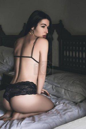 Photo pour Sexy jeune femme en lingerie regardant loin tout en étant assis sur le lit - image libre de droit