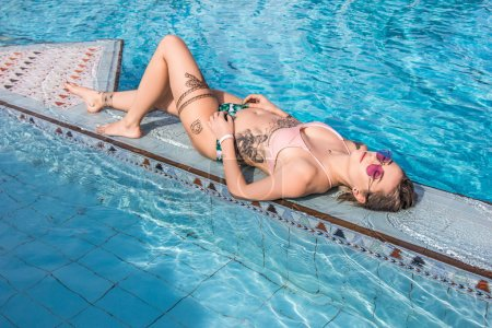 Photo for Beautiful seductive young woman in sunglasses and swimwear lying at swimming pool - Royalty Free Image
