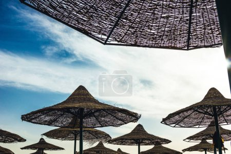 Photo for Wicker umbrellas on beach at resort in Egypt - Royalty Free Image