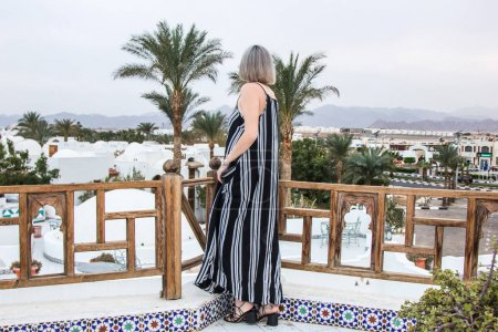 rear view of woman in dress looking at resort in Egypt