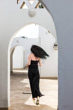 Photo pour Vue arrière de la jeune femme courant au bâtiment blanc en Egypte - image libre de droit
