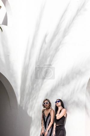Photo pour Attrayant filles à la mode dans des lunettes de soleil posant près de bâtiment blanc à la station balnéaire en Egypte - image libre de droit