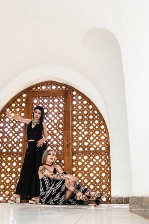 beautiful stylish girls looking at camera and posing near decorative wooden gates in Egypt