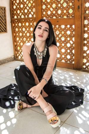Photo pour Attrayant fille regardant caméra tout en étant assis près des portes en bois décoratives en Egypte - image libre de droit