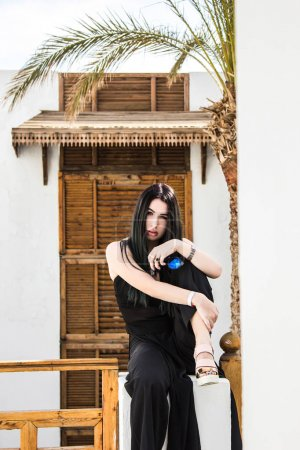beautiful girl holding sunglasses and looking at camera while sitting at resort in Egypt