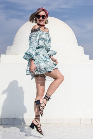 Photo pour Heureuse belle fille en robe et lunettes de soleil sautant et souriant à la caméra près du bâtiment blanc en Egypte - image libre de droit