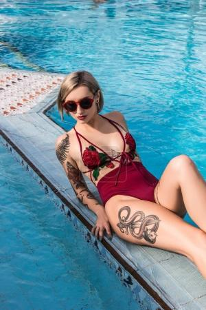 Photo for Beautiful girl in sunglasses and swimsuit resting at swimming pool - Royalty Free Image
