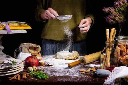 Photo for Cropped shot of person sifting flour on dough at table with ingredients - Royalty Free Image