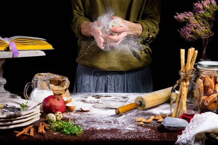 partial view of human hands preparing dough at table with ingredients