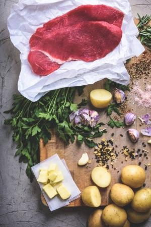 Photo for Top view of potatoes, butter, wooden spoon with tomato sauce, spices and raw meat on cutting board - Royalty Free Image