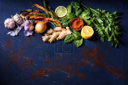 Photo for Top view of parsley, basil, lemon, peppers, onion, garlic and ginger on blue - Royalty Free Image