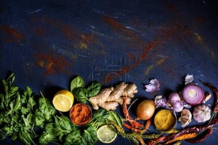top view of tasty healthy herbs, vegetables and spices on blue