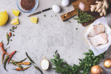 Photo for Top view of raw fish fillet in bowl with vegetables and spices on grey surface - Royalty Free Image