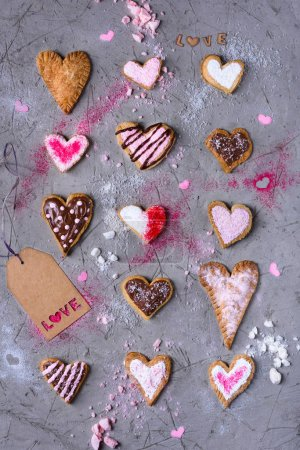 Photo for Top view of sweet traditional heart shaped cookies with love tag on grey cracked surface - Royalty Free Image