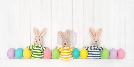 Photo pour Oeufs de Pâques et drôle de décoration de lapin sur fond blanc en bois - image libre de droit
