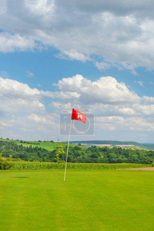 Photo pour Terrain de golf avec l'herbe verte, drapeau rouge et ciel bleu nuageux. Parcours de golf - image libre de droit