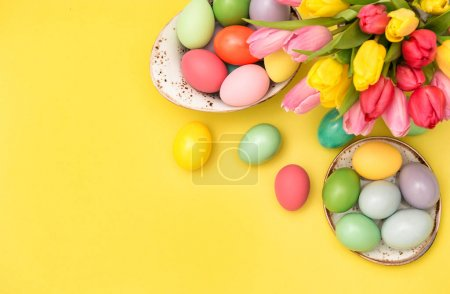 Photo for Easter eggs decoration and tulip flowers on yellow background - Royalty Free Image