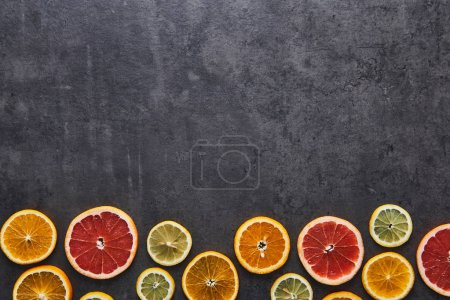 Photo for Flat lay of citrus fruits pattern of lemon, orange and grapefruit on black stone background. Copy space above. Top view. - Royalty Free Image