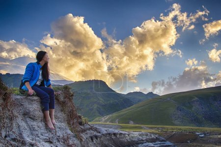 Woman in the mountain landscape at the sunset